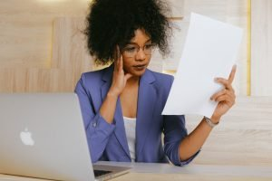 woman with laptop frustrated by paperwork