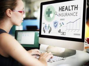 woman checking health insurance on computer monitor